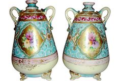 Beautiful pair of 19th-century vanity vases with floral motifs and gold stippling. Each has three small feet. Believed to be Nippon, but the only maker's mark is a red line across the base.