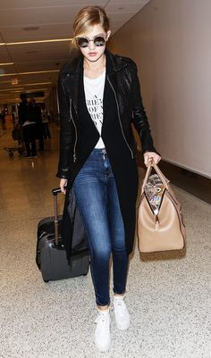 Gigi Hadid wears a graphic t-shirt, long black coat, skinny jeans, white sneakers, satchel, and round sunglasses