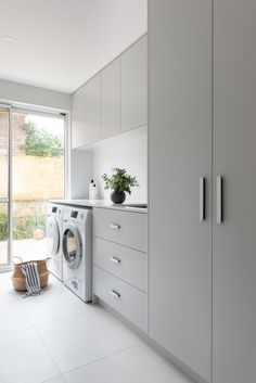 A laundry makeover that's practical, functional AND beautiful. Contemporary and elegant laundry makeover by Jane Ledger Interiors. Soft grey and white modern laundry. Laundry with white kitkat tile mosaic splash back. Simple rounded door handles in laundry.