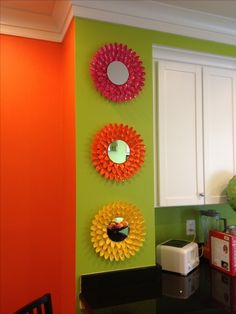 "3 ""daisy"" mirrors made from colored plastic spoons glued to cardboard circles."