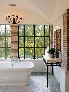 The brick columns contrast with the white walls and make the bathroom feel more cozy. A candle sconce light above the luxurious freestanding tub adds a warm, traditional touch to the room, while large windows bring in plenty of natural light. A gray tile border on the floor visually frames the area to make this spacious bathroom more intimate.