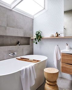 Modern bathroom with a gray rectangle tile on one wall and a white hexagon tile behind the sink.