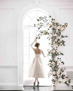 Create your own rosy red-carpet moment for your ceremony backdrop. Work with a preexisting doorway or a similar freestanding structure. To create the illusion of a trailing vine, secure each rose and lisianthus to leafy camellia branches. When hung on the molding using adhesive hooks, they form a stunning design.