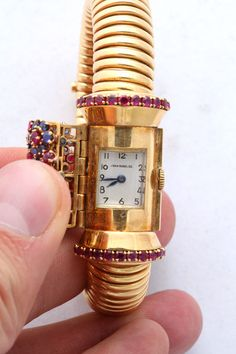 John Rubel Gold, Ruby, Diamond and Sapphire Bracelet Watch with Concealed Dial | From a unique collection of vintage wrist watches at http://www.1stdibs.com/jewelry/watches/wrist-watches/