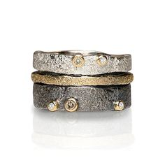 Bedrock Stacking Bands by Jenny Reeves. Rings of bright and oxidized sterling silver and 18k gold are enlivened with scintillating, organic texture. Bright sterling silver band has 1.7mm champagne and 1.3mm white diamonds. Oxidized sterling silver band has 2mm and 1.7mm champagne and 1.3mm white diamonds. Sold individually. Available in whole, half, and quarter sizes 4–9. Total height of stack is 10mm.