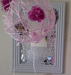 Decorative ball made from, a ballon wrapped in knitting yarn (wool) that was dipped in a cornflour and glue mixture. Decorated with tissue paper flowers and ribbon.