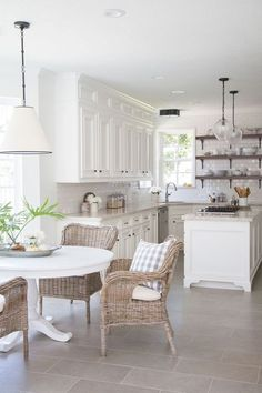 All-white farmhouse kitchen with wicker furniture and gray tile floors.