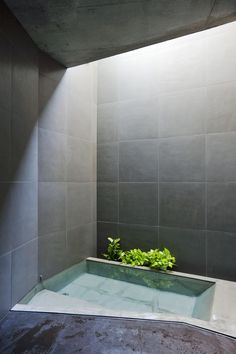 The Art of the Japanese Bath | Sky Garden House  by Keiji Ashizawa Design.  This house for a young family and their parents is located in a residential neighborhood in Tokyo. The bathroom is located beneath the ground, along the sloping street. The enclosed space receives natural light from a top light, which gives the dark-grey-tile-clad room an austere atmosphere.