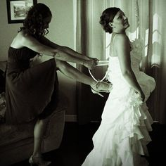 My Sister fixing my dress. We posed for this picture, but it is still funny every time I see it.