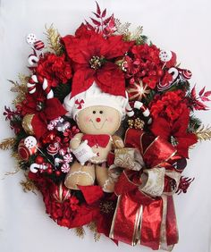 "The wreath is embellished with red Poinsettias, red/gold shatterproof Christmas Ornaments, red and gold sparkle Christmas leaves. The wreath is accented with a lovely Gingerbread Man, Christmas Peppermints and Candy cans . I finish the wreath with a red/gold/cream Ribbon Bow.   The wreath measures from tip to tip at 27"" (L) x 26"" (W) x 8""(D)."