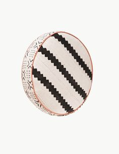 """Black and white roundpillow with pink piping made from traditional """"mud cloths"""" from Ghana. These pillows are special edition.  Measures approximately15"""" x 15"""