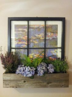 Poster framed behind an old window sash. Made a planter box from old fence boards and added flowers/plants.