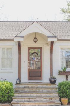 White brick cottage portico front porch exterior with floral front door wreath, stained wood 6 lite glass door, flagstone steps, stained columns, wooden window boxes, nautical copper exterior light. Benjamin Moore Soft Chamois white paint. Jacobean and natural wood stain mix. Spring Green shutters. Arched entry.