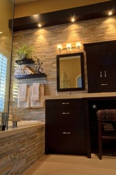 Soft lighting, neutral colors, stone tub and walls, and dark wood. Love it!