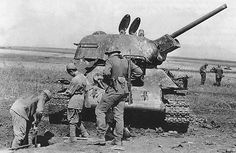 WW2. Soviet POW's burry their comrade next to knocked out T-34