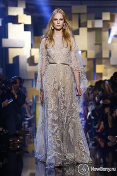 Collection of beautiful evening dresses Haute Couture Fall-Winter 2015-2016 by Lebanese designer Elie Saab. The famous fashion designer once again delights and surprises for his work. Models shone on the catwalk in translucent evening gown with a long train, strewn with loose sparkling crystals, appliqués and prints of large flowers, and hair gleamed golden tiaras, which are quite distinct addition to the spectacular evening show images of Elie Saab.