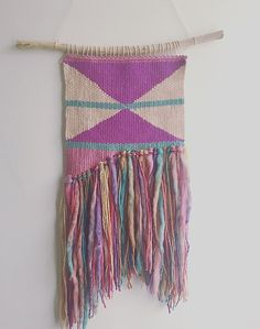 This beautiful woven wall hanging is made with the cutest rainbow yarn. It measures approx 21cm x 50cm including the fringing. Its handmade and hung on a natural stick.
