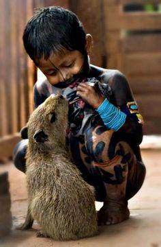Niño sudamericano con capibara. Estos grandes roedores, se usan como mascotas en zonas selvaticas