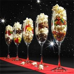 Oscars Popcorn Bar : Set the table with a black table cloth, roll out the red carpet (or ribbon) and line up the stars of the night: champagne glasses filled with popcorn and candies. Put any extra popcorn and candies in decorative bowls for a DIY popcorn bar