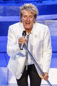 Stylish: Dressed in a white jacket with white shirt and stripy monochrome tie, which he teamed with black cigarette pants, the crooner looked every inch the  rock star on stage at the packed arena