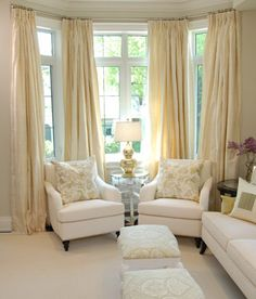living rooms - silver lamp chair set soft butter yellow silk drapes gold gourd lamp bay window ottomans Yellow silk drapes, white curvy chairs