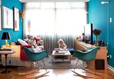 Entre os móveis da sala em tons de azul reina o cão Francisco. A cortina de linho cru, da NP Decorações, quebra a entrada de luz. Nas paredes, o turquesa escuro é da tinta R327, da Suvinil. Cadeiras de balanço Charles Eames, da Desmobilia. Luminárias da Reka.  Fotos Lufe Gomes
