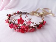 A luxuriously ornamental halo made of tangly berry vines and cherry blossoms. The hand-woven design features curly twigs with antique-gold and pink berries. Flowers are in shades of bright and light pink.  Adjustable ribbon tie closure, or you may order in headband length and pin the ends to secure. For added embellishment with Swarovski pearls or crystals, please inquire before ordering.  Color: pink and gold  Materials: silk-like flowers  Hand crafted in my Missouri studio,  of imported…