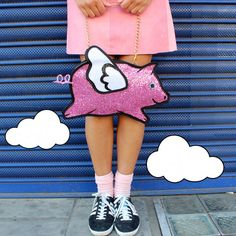 A flying pig shaped clutch handbag.  The 2D pig is made from a bright bubble gum pink and pearl white glitter fabric, bound in black satin and