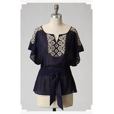 """FLOREAT Anthropologie EMBROIDERED Navy Blue Blouse FLOREAT Anthropologie EMBROIDERED Navy Blue Blouse. Sz Sbust 32-34Length 25""""Front tieShort sleeve SMALL HOLE PLEASD SEE PICTURE 3❗️ The heart shows where the hole is...price reflects! Anthropologie Tops"""