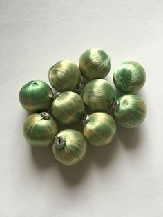 Shatterproof satin covered foam ornaments. https://www.etsy.com/listing/482995213/set-of-10-vintage-green-and-gold-satin