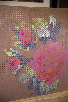 Painted cross stitch on peg board [or you could use yarn and stitch it, other pins of that are around]