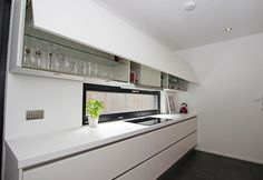 White satin lacquer kitchen design in a  handleless style with a white Corian worktop. Also includes pan drawers for storage and wall units ith automatic uplift doors.