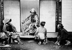 Man dressed in samurai armor is waited upon by woman serving tea. Two retainers are seated on the left and right of the samurai. Possible indoor studio setting. Old Japan.