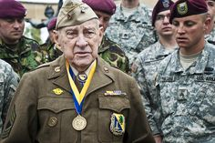 World War II veteran, Sgt. Maj. Raymond Sylvester, regales paratroopers from the U.S. Army Civil Affairs and Psychological Operations Command at the American cemetery in Normandy, France, June 6, 2011. These paratroopers are members of Task Force Normandy, which is a multinational force of U.S., U.K., French, and German soldiers, sailors, and airmen in a combined effort to remember and celebrate the 67th Anniversary of the D-Day operations.