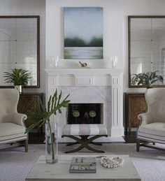 Beautiful living room boasts a blue and green canvas landscape art piece placed over a white fireplace mantle accented with raised panel trim and a white marble surround flanked by antique French mirrors and cabinets finished with sunburst doors. Fireplace With Cabinets, Fireplace Mirror, White Fireplace, Living Room With Fireplace, Fireplace Surrounds, Living Room Mirrors, Living Room Art, Home And Living, Living Spaces