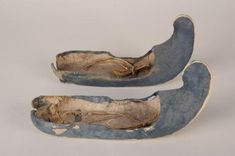 Tang Dynasty. The shoes have a surface of blue silk and a flat bottom. The shoes are made of four pieces of cotton cloth, but the soles, the topcover and the ends are made out of one piece. A long thin white silk thread is stuck to the toes as a decoration. Two thin ropes are tied to the back of the shoes. Unearthed from tomb No. 27 of the Astana Cemetery in Turpan, Gaochang. Xinjang Uygur Autonomous Region.