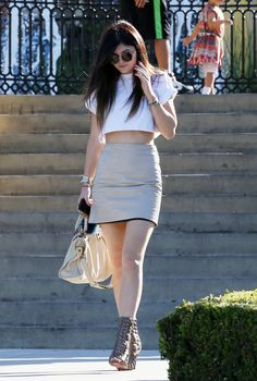Love their style. Kylie Jenner was seen leaving a restaurant with some friends as she donned a white crop top t-shirt, a nude leather pencil skirt, and some Christian Louboutin open-toed booties.