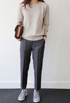 Picture Of a neutral cashmere sweater, grey trousers, grey sneakers and a brown leather bag for a relaxed work look