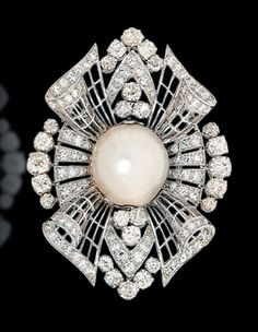 An Art deco natural pearl and diamond brooch. The openwork navette shaped panel…