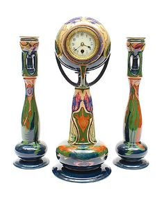 Polychrome decorated 3-piece clock garniture consisting of a clock and two candle-holders executed by Plateelbakkerij Zuid-Holland Gouda / the Netherlands ca.1905