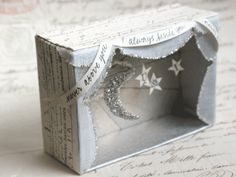 "mini diorama with glittered moon and stars embellished with printed ribbon with saying "" never above you always beside you"" made by D Sharp"