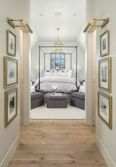 Pine wood floors separated shiplap hallway walls accented with gold leaf framed black and white photography lit by brass picture lights.