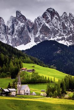 view of the picturesque church of St. Magdalena in the Val di Funes, Italy. The hills are covered in yellow dandelions and those jagged peaks in the background are the Dolomites.