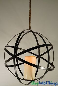 Rustic vintage charm meets romantic candlelight glow in this contemporary Hanging Metal Sphere with Candle! This decorative hanging orb with a large flickering flameless candle is chic en Hanging Candles, Votive Candles, Decorative Spheres, Hanging Terrarium, Beaded Curtains, Metal Candle Holders, Tea Light Holder, Event Decor, A Table