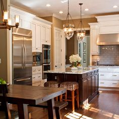 Like the wall color in the kitchen with white cabinets. Love the lights over the island too....