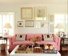 Wood and shell tabletop decor in the home of India Hicks.  Coastal shabby chic pink slipcover sofa with geometric print pillows.