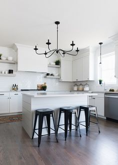 White kitchen contrasted with black accents boasts three black Tolix stools placed at a white shiplap island topped with a white quartz countertop illuminated by a wrought iron chandelier. Rustic Kitchen Design, Home Decor Kitchen, Kitchen Furniture, Kitchen Ideas, Outdoor Furniture, Cheap Furniture, Kitchen Designs, Stools For Kitchen Island, White Kitchen Island