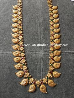 Different design South Indian mango mala haram with flower embossing on each paisley shape. Adorned with rubies, emeralds and CZs, this simple haram weight 65 gms. Jewelry Design Earrings, Gold Earrings Designs, Necklace Designs, Jewellery Designs, Latest Jewellery, Gold Temple Jewellery, Gold Wedding Jewelry, Gold Jewelry, Mango Mala Jewellery