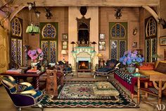 At Pierre Bergé's estate in Normandy, France, antique stained-glass doors and pine paneling line the multipurpose salon of the Russian-style main building, which was created in the 1980s for Bergé and his late partner, the fashion designer Yves Saint Laurent. The carpet is 19th-century Russian, as are the table at left and the carved bench beside it. Guests can also relax on the elegant floor cushion.