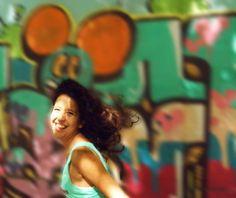 Escenario: Mural de la escuela de mi barrio, escenas varias para retratar a mi hija. Encuadre: plano pecho, cámara ángulo normal. Mi hija salta y le tomo una instantánea en movimiento. Vestuario: normal. Iluminación:luz natural suave y luz dura en el rostro.  Retoque: trabajo en capas para desenfocar el fondo y dar efecto de movimiento.